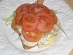 Læg tomatskiver på, og giv dem et drys salt.