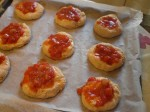Kom tomatsauce på pizzabollerne.