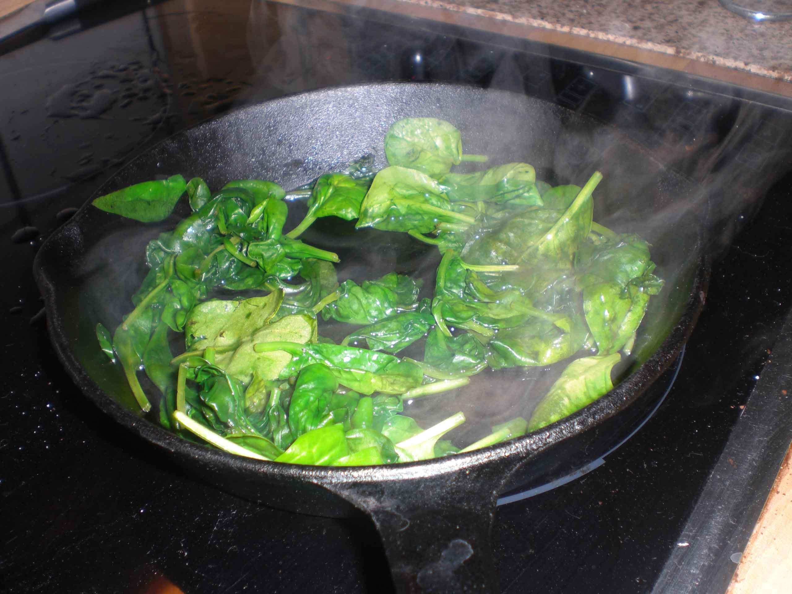Damp spinaten på en meget varm pande.