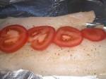 Drys med krydderier, og fordel tomatskiver på fisken.