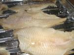 Læg halvdelen af fiskefileterne ved siden af hinanden i en grillbakke.
