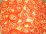 Fordel tomatskiverne på pizzaen, og dernæst resten af osten.