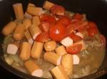 Tilsæt pølser og tomater.