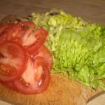 Skær tomater i skiver, og salat i strimler.