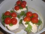 Læg basilikum og halverede cherrytomater oven på.