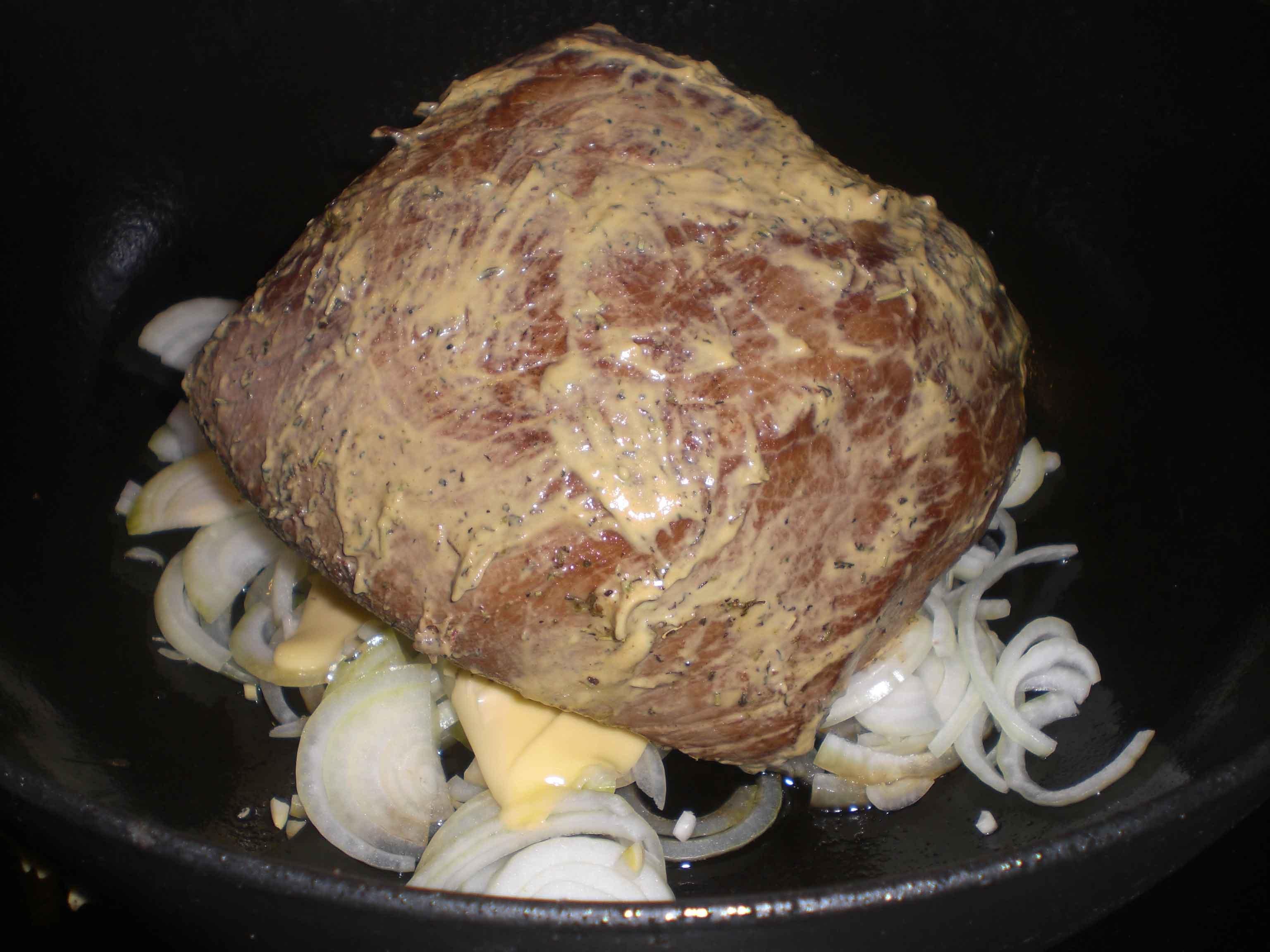 Læg løg, smør og det krydrede kød i gryden.